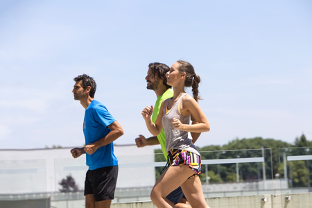 Two young men and woman running in urban enviroment at hot summer day