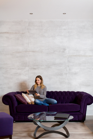 Young woman with tablet on violet color sofa