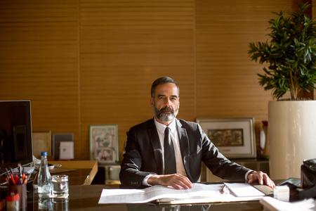 Senior businessman working on laptop in modern office at desk
