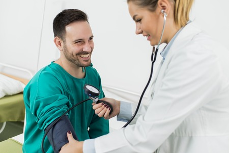Female doctor checking blood pressure of a patient at clinic Stockfoto