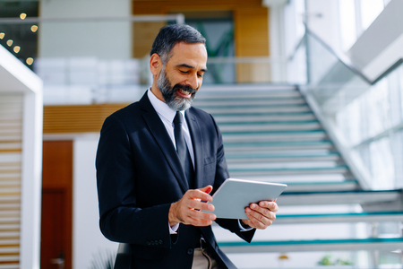 Bel homme d'affaires d'âge mûr avec tablette numérique dans le bureau de Modren