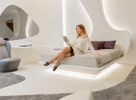 Young woman in dress using digital tablet in modern futuristic bedroom