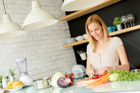 近代的なキッチンで健康的な食事を準備するかなり若い女性