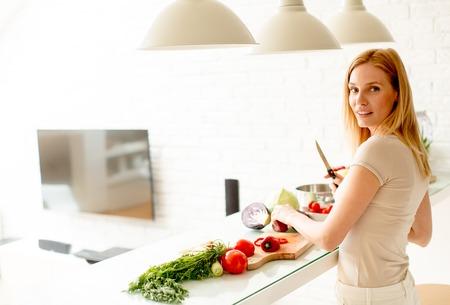 かなり若い女性のモダンなキッチンで健康的な食事の準備