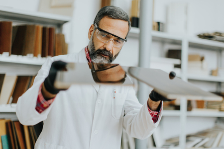 Handsome mature engineer testing colors on wooden specimens in the furniture factory