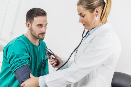 Female doctor checking blood pressure of a patient at clinic Stock Photo