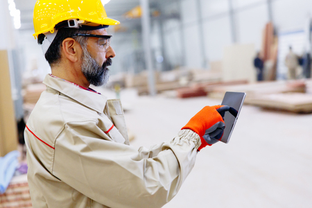 Handsome mature engineer in the factory with digital tablet