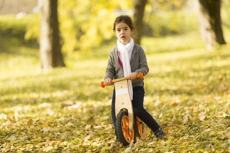 View at little girl riding bicycle in autumn park Stock Photo