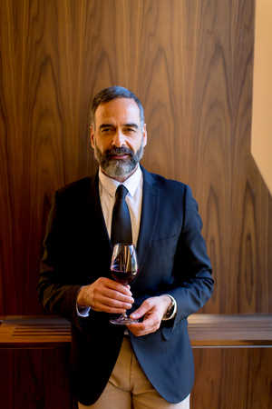 Portrait of handsome man with glass of red wine