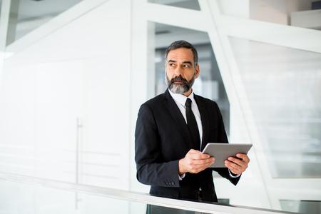 モドレンオフィスでデジタルタブレットを持つハンサムな中年のビジネスマン