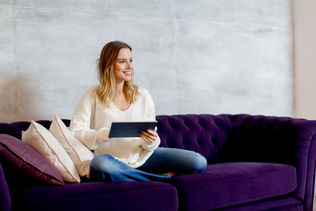 Young woman with digital tablet on sofa