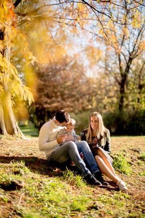 Blick auf junge Familie sitzt auf dem Boden im Herbst Park Standard-Bild - 93228331