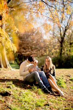 View at young family sitting on the ground in autumn park Foto de archivo