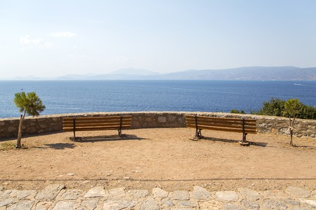 View at seaside viewpoint with benches on Hydra island in Greece Stock Photo