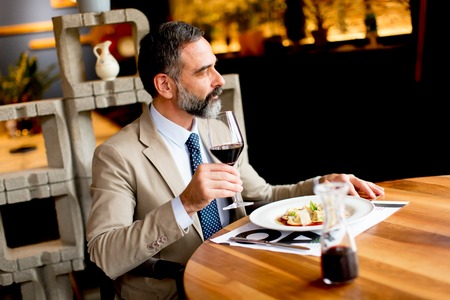 Handsome mature man drinking red wine during lunch Reklamní fotografie