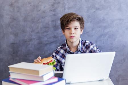 Portrait of teenage boy eats a sandwich and web-surfing