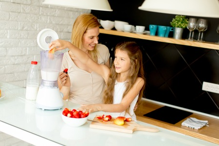 Mother and daughter preparing healthy juice from fresh ingredients in the kitchen Stock Photo