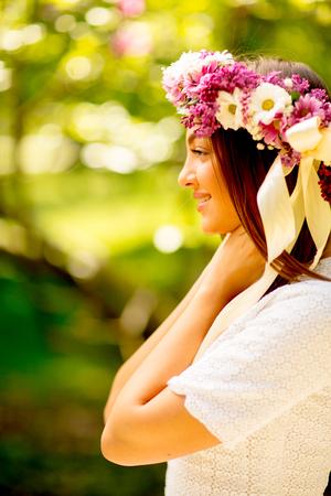 Portret van jonge vrouw met kroon van verse bloemen op hoofd in het park Stockfoto