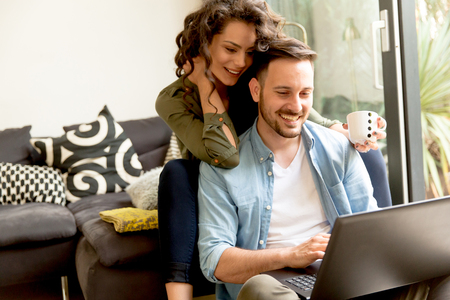 Young couple sitting on floor and using notebook. Online shopping Archivio Fotografico