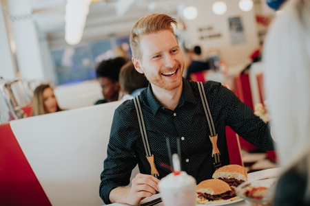 Young man eating beef cheeseburger in diner