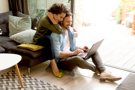 Young couple sitting on floor and using notebook. Online shopping Foto de archivo