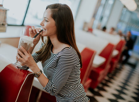 Woman with glass of milkshake at the diner Stock Photo