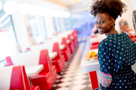Portrait of young african american woman eating in the diner