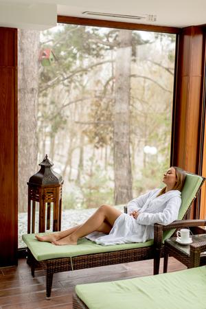 冬の屋内スイミングプールのそばのデッキチェアでくつろぐ可愛い若い女性 写真素材