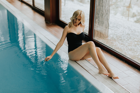Pretty young woman sitting by the swimming pool Stock Photo
