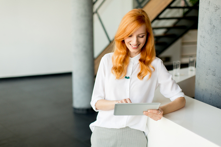Pretty young red hair woman using digital tablet in the modern office Foto de archivo