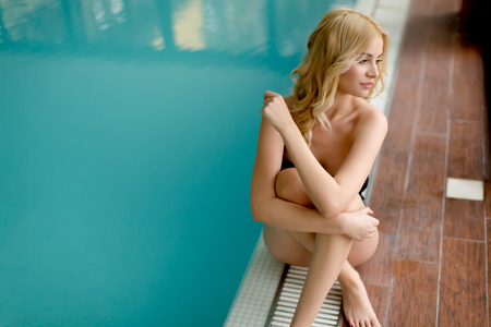 Pretty young woman relaxing by swimming pool in spa center