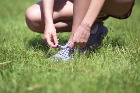 Young woman binds her shoelaces on the sneakers in the park Stock Photo