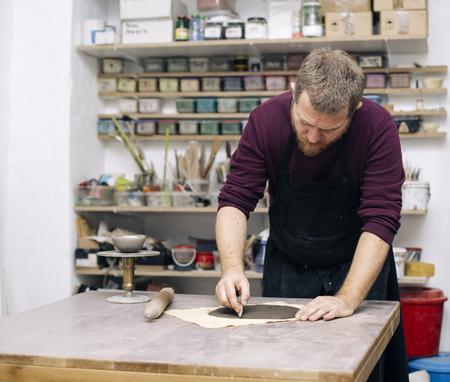 彼の作品のための粘土のワークを準備する熟練したマスターでビューをクロース