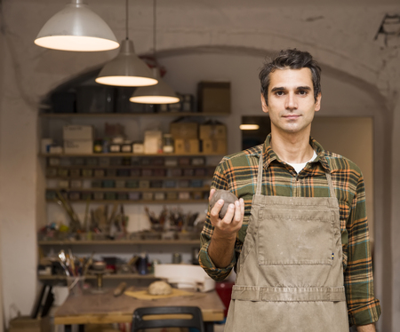 Portrait of handsome young man in pottery workshop holding clay
