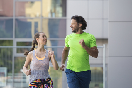 Couple running in urban enviroment  at hot summer day