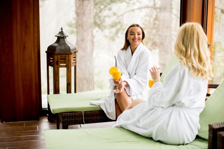 Two cheerful women in bathrobes drinking juice in spa center