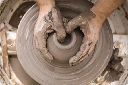 アーティストのクローズアップディテールビューは、スピンホイール上の粘土陶器を作ります 写真素材