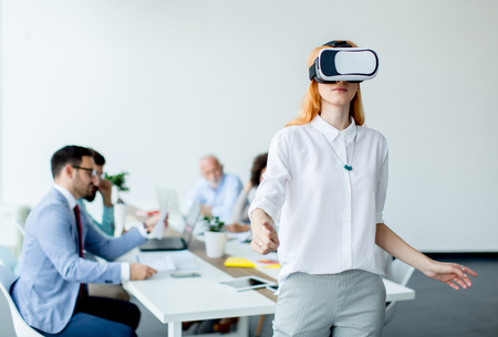 Young woman using virtual reality simulator during meeting in the office