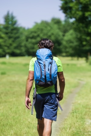 Back view at young man with backpack hiking at green nature