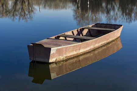 Small wooden boat on the calm lake