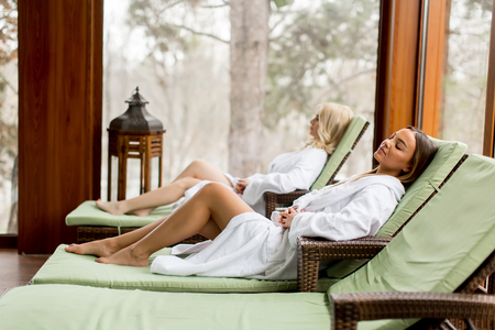Pretty young women relaxing on the deckchair by the swimming pool in spa 스톡 콘텐츠