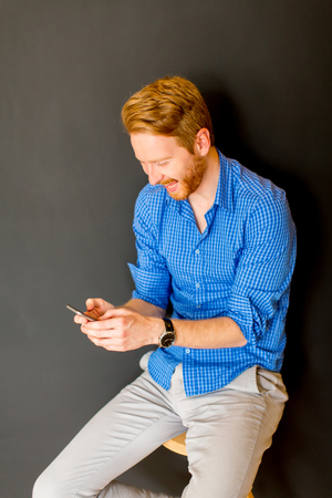 Portrait of redhair man with mobile phone by wall