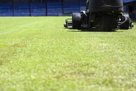 View at lawnmower cutting grass on the football stadium