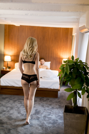 Young man is waiting for a sexy woman in bed at home