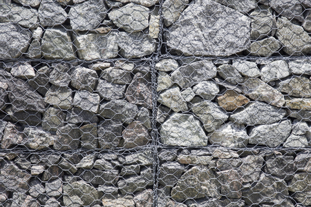 Closeup of the old stone wall behind iron net protection