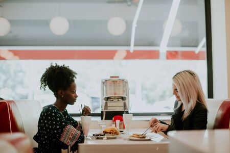 Multiracial female friends eating fast food at a table in the diner and have fun