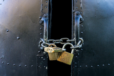 View at metallic locked door with three padlocks Stockfoto