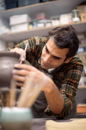 Young man making and decorating pottery in workshop