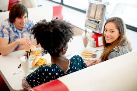 Group of young multiracial friends enjoying in the diner