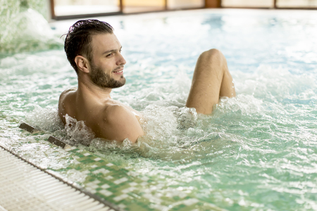 Handsome young man relaxing in hot tub in spa Stok Fotoğraf - 96768702